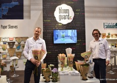 "Olaf Amende and Thomas Leithe of Weber Verpackungen presenting their new and potential products in the bloomguard range. Leithe is holding the paper sleeve for lettuce and Amende the sleeve made out of a transparent glassine paper. ""The consumer wants to see the flowers and with glassine paper on the top, the consumer can still see the flower and no plastic is used. So far, they received positive reactions, and they will now test how it will work in practice. Amende has high expectations particularly when used to sleeve mono bunches."