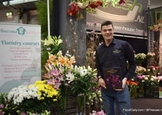 "Levi Evers of Bredefleur at the booth of G Fresh, according to Evers the only platform that displays the harvest date of the flowers. He is standing next to one of their new white varieties, namely Genzano. ""It has a purely white flower."""